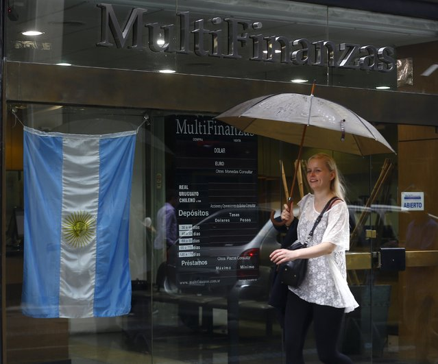 A woman walks past a currency exchange rates board at a money exchange in Buenos Aires' financial district, Argentina, December 17, 2015. Argentina's peso plunged 29.8 percent at the start of trade on Thursday, in line with expectations, after the country's new government floated the currency as part of a slew of free-market reforms aimed at revitalizing the stagnant economy. (Photo by Enrique Marcarian/Reuters)