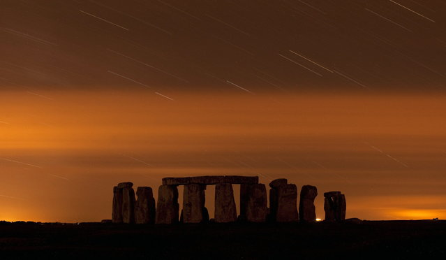 A general view of Stonehenge during the annual Perseid meteor shower in the night sky in Salisbury Plain, southern England August 13, 2013. The Perseid meteor shower is sparked every August when the Earth passes through a stream of space debris left by comet Swift-Tuttle. Picture taken using a long exposure. (Photo by Kieran Doherty/Reuters)