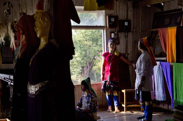 An ethnic Kayan-Padaung woman in traditional attire weaves at a souvenir shop as others watch in Ywama village, Inle Lake, northeastern Shan state, Myanmar, Monday, February 16, 2015. (Photo by Gemunu Amarasinghe/AP Photo)
