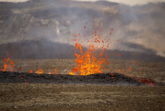 Steam and lava spurt from a new fissure on a volcano on the Reykjanes Peninsula in southwestern Iceland, Monday, April 5, 2021. (Photo by Marco Di Marco/AP Photo)