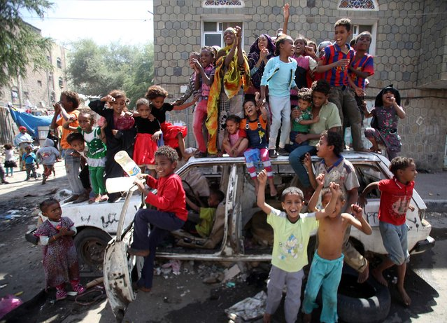 Children play on an abandoned car near a protest, which is against the dissolution of Yemen's parliament and the Shi'ite Muslim Houthi militia's tightening grip on power, in the southwestern city of Taiz, February 13, 2015. (Photo by Mohamed al-Sayaghi/Reuters)