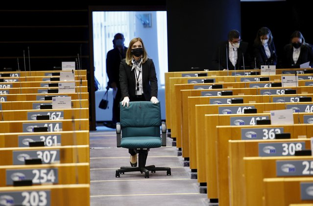 A parliamentary worker wheels a rolling chair down the aisle of the plenary chamber ahead of a debate on Turkey at the European Parliament in Brussels, Monday, April 26, 2021. (Photo by Olivier Matthys/AP Photo/Pool)