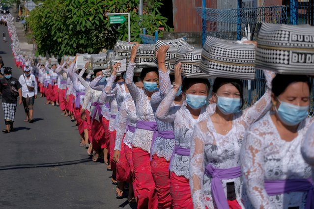 Balinese Hindus wearing protective masks carry offerings as they celebrate the Galungan religious holiday at Lukluk village, amid the coronavirus disease (COVID-19) pandemic, in Badung, Bali, Indonesia on April 14, 2021. (Photo by Nyoman Hendra Wibowo/Antara Foto via Reuters)