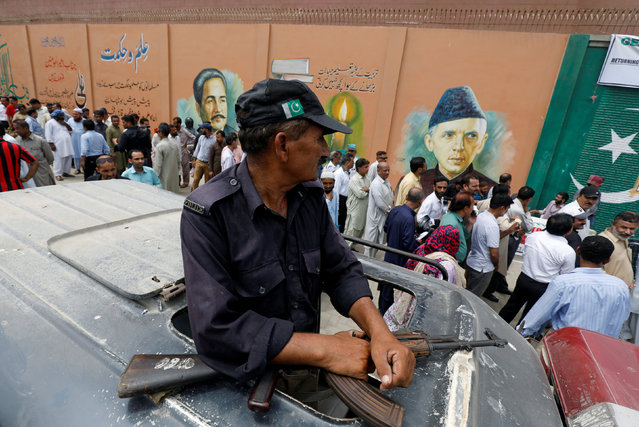 A police officer guards, where electoral workers stand in line to collect election materials ahead of general election in Karachi, Pakistan July 24, 2018. (Photo by Akhtar Soomro/Reuters)
