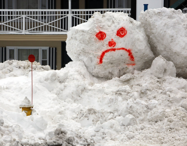 A snowman's face is seen in front of a hotel Wednesday, February 18, 2015, in Hampton, N.H.  after several feet of snow has fallen in the last couple of weeks. (Photo by Jim Cole/AP Photo)