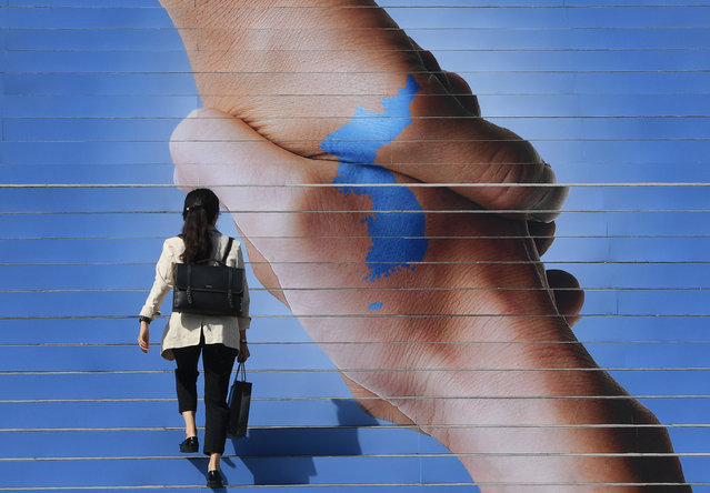 A woman walks on the stairs decorated with an image of two hands shaking to form the shape of the Korean Peninsula to support the upcoming inter- Korean summit, in downtown Seoul on September 17, 2018. South Korean President Moon Jae- in will fly to the North Korean capital on September 18, for his third summit with the North' s leader Kim Jong Un as a rapid diplomatic thaw takes hold on the peninsula despite stalled progress in denuclearisation talks between Pyongyang and Washington. (Photo by Jung Yeon-je/AFP Photo)