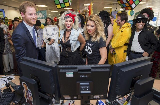 Britain's Prince Harry takes part in a charity trading day at ICAP with Kate Arnold and Samantha Bennett on the EBS Direct Desk in support of his charity Sentebale, in London, December 7, 2016. (Photo by Geoff Pugh/Reuters)