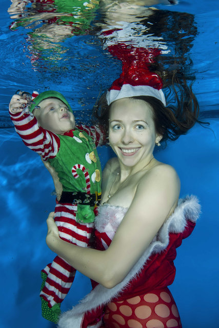 Mom dressed as Santa and a boy dressed as Santa's helper posing under the water in the pool on December 15, 2016 in Odessa, Ukraine. (Photo by Andrey Nekrasov/Barcroft Images)