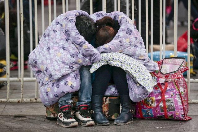A couple share a quilt at midnight at a railway station in Guangzhou, Guangdong province, January 25, 2016. According to traffic police, over 2.9 billion trips will be made around China during the 40-day Spring Festival travel rush started on January 24. (Photo by Reuters/China Daily)