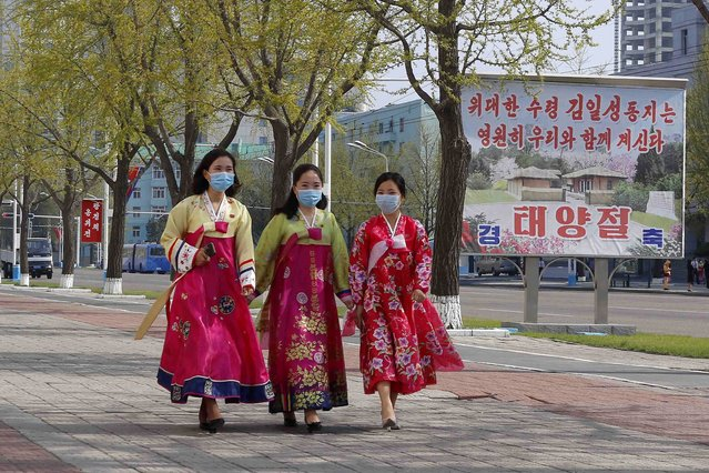 """Women walk in a street near the Arch of Triumph on the Day of the Sun, the birth anniversary of late leader Kim Il Sung, in Pyongyang, North Korea Thursday, April 15, 2021. The poster reads """"The great leader Comrade Kim Il Sung will always be with us. Day of the Sun"""". (Photo by Cha Song Ho/AP Photo)"""