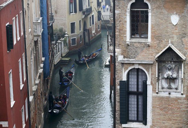 Gondoliers row along a canal near St. Mark's Square in Venice January 30, 2016. (Photo by Alessandro Bianchi/Reuters)