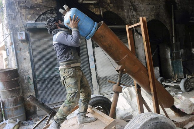 A Free Syrian Army fighter prepares a locally made shell before launching it towards forces loyal to Syria's president Bashar Al-Assad in Old Aleppo January 17, 2015. (Photo by Abdalrhman Ismail/Reuters)