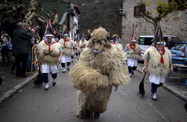 A man dressed in a bear costume performs alongside dancers during carnival celebrations in Ituren February 1, 2016. (Photo by Vincent West/Reuters)