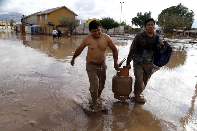 Locals carry a gas bottle on a flooded street at Copiapo city, March 26, 2015. (Photo by Ivan Alvarado/Reuters)