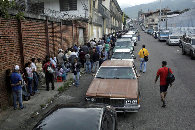 People line up outside a supermarket next to motorists queuing for gas near a gas station of the Venezuelan state-owned oil company PDVSA in San Cristobal, Venezuela on November 13, 2018. (Photo by Carlos Eduardo Ramirez/Reuters)