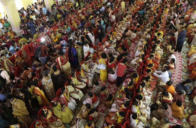 """Young Hindu girls sit together for a ceremony where they are worshipped as """"Kumari"""", or living goddess, during Ram Navami festival, at a temple in Kolkata, India, Saturday, March 28, 2015. (Photo by Bikas Das/AP Photo)"""