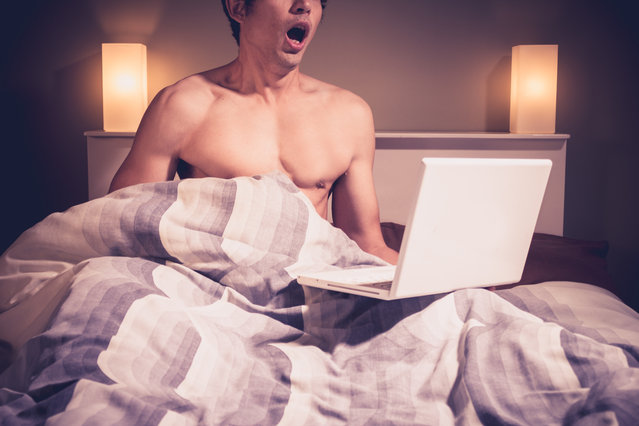 Young man is sitting in bed and watching p*rnography on his laptop. (Photo by Getty Images/iStockphoto)