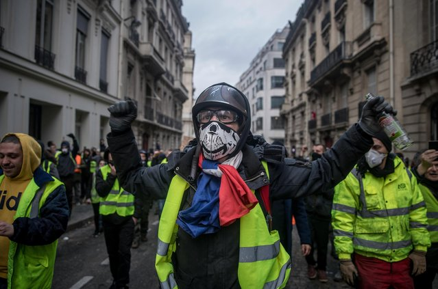 "Protesters march in the ""yellow vests"" demonstration near the Arc de Triomphe on December 8, 2018 in Paris France. (Photo by Chris McGrath/Getty Images)"
