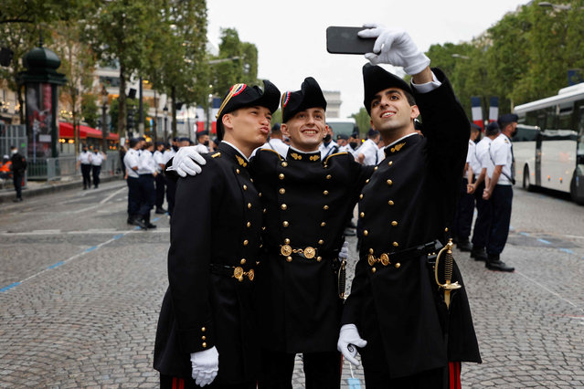 Pupils of the Ecole Polytechnique (Special military school of Polytechnique) pose for a picture as preparations are made for the annual Bastille Day military parade on the Champs-Elysees avenue in Paris on July 14, 2021. (Photo by Ludovic Marin/AFP Photo)