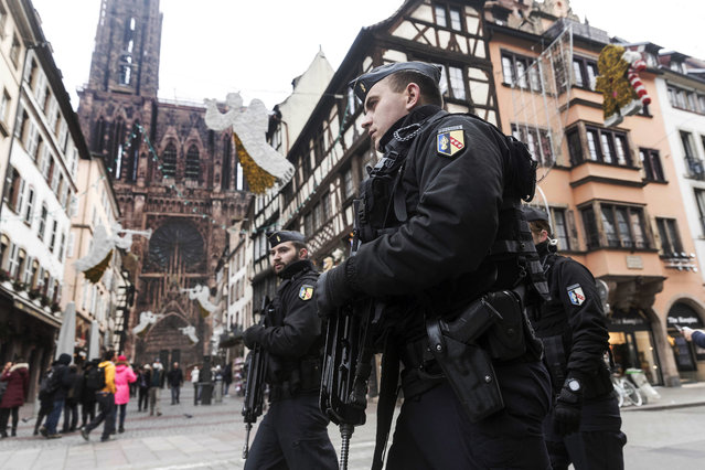 French police officers patrol next to Notre-Dame cathedral of Strasbourg following a shooting in the city of Strasbourg, eastern France, Wednesday, December 12, 2018. A man who had been flagged as a possible extremist sprayed gunfire near the city of Strasbourg's famous Christmas market Tuesday, killing three people, wounding 12 and sparking a massive manhunt. France immediately raised its terror alert level. (Photo by Jean Francois Badias/AP Photo)