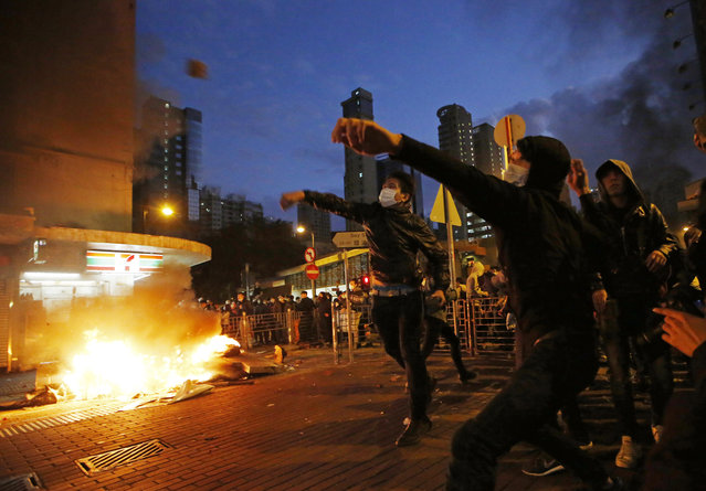 Rioters throw bricks at police and lit fires on streets in Mongkok district of Hong Kong, Tuesday, February 9, 2016. (Photo by Kin Cheung/AP Photo)