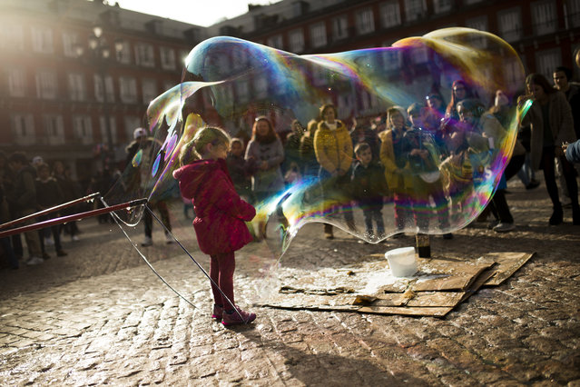 A child stands inside a large soap bubble made by a street artist at the Mayor square in central Madrid, Friday, December 9, 2016. (Photo by Francisco Seco/AP Photo)