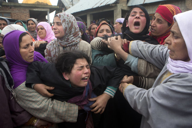 Unidentified women try to comfort Asmat shafi, center in black, and Sakeena Shafi, third right in black, during the funeral procession of their father Mohammad Shafi, an Indian policeman killed in a gunbattle, in Chenabal, some 21 Kilometers north of Srinagar, Indian controlled Kashmir, Thursday, April 2, 2015. (Photo by Dar Yasin/AP Photo)