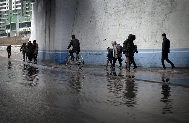North Koreans walk along a flooded street on Sunday, February 14, 2016. (Photo by Wong Maye-E/AP Photo)