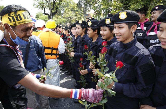 An anti-government protester gives roses to Thai policewomen outside city police headquarters in Bangkok, Thailand Tuesday, December 3, 2013. Anti-government protesters swarmed into the Thai prime minister's office compound Tuesday as police stood by and watched, allowing them to claim a symbolic victory after three days of bitter clashes. (Photo by Manish Swarup/AP Photo)