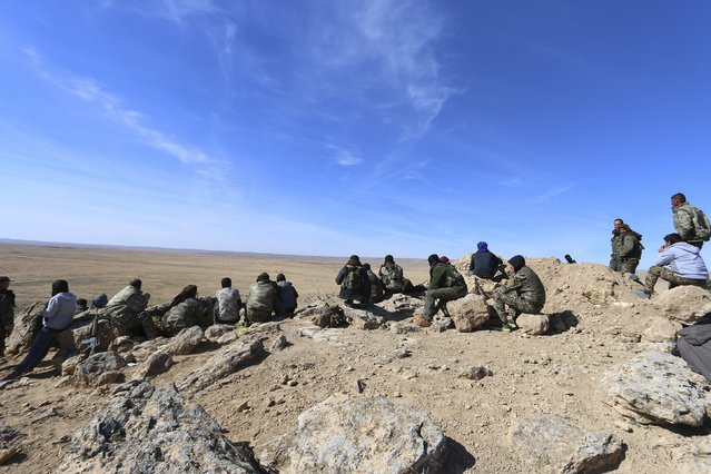 Fighters from the Democratic Forces of Syria stand on a lookout point to watch for Islamic State fighters in the southwestern countryside of Hasaka, Syria February 17, 2016. Picture taken February 17, 2016. (Photo by Rodi Said/Reuters)