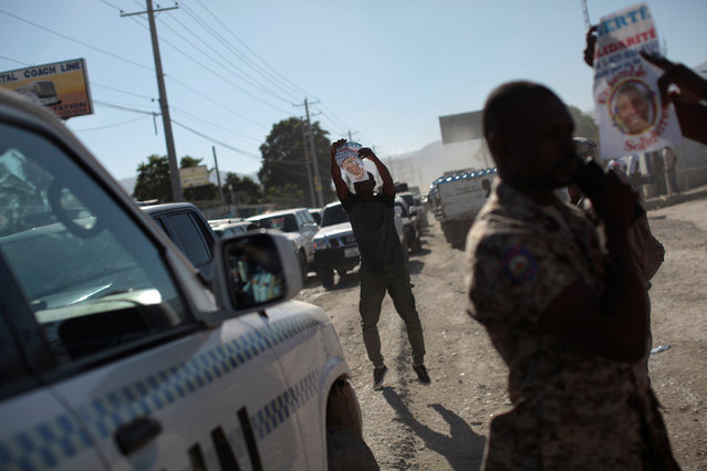A supporter of Haitian Senator-elect Guy Philippe, who was arrested and extradited to the United States last week, tries to stop a United Nations car during a protest in front of the U.S. embassy in Port-au-Prince, Haiti, January 13, 2017. (Photo by Andres Martinez Casares/Reuters)