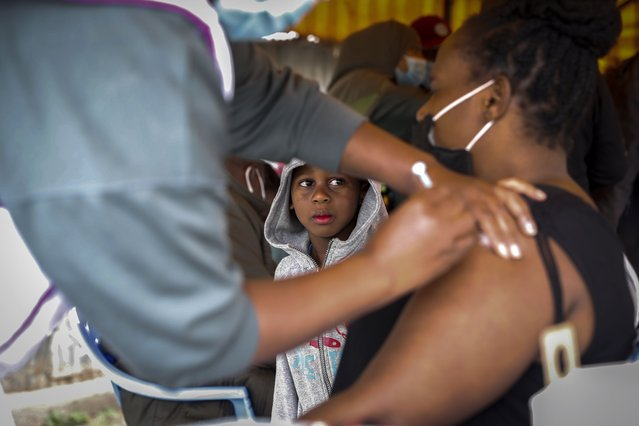 A Kenyan woman receives a dose of AstraZeneca coronavirus vaccine donated by Britain, as her son watches, at the Makongeni Estate in Nairobi, Kenya Saturday, August 14, 2021. In late June, the international system for sharing coronavirus vaccines sent about 530,000 doses to Britain – more than double the amount sent that month to the entire continent of Africa. It was the latest example of how a system that was supposed to guarantee low and middle-income countries vaccines is failing, leaving them at the mercy of haphazard donations from rich countries. (Photo by Brian Inganga/AP Photo)