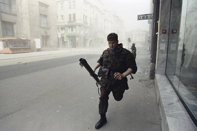 A Muslim militiaman sprints for cover after a tank round, fired by Yugoslav federal army, struck an apartment house across the street in Sarajevo on Saturday, May 2, 1992. The Yugoslav Army attacked the Bosnian capital with mortar rounds and heavy artillery after Muslim forces surrounded the army's barracks here. (Photo by David Brauchli/AP Photo)