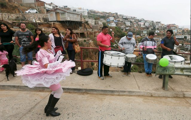 A member of a dancing group performs to commemorate victims of a fire at a neighborhood on a hill in Las Canas, an area which was also affected by the fire, in Valparaiso April 12, 2015. This Sunday marks the first anniversary of the deadly wildfire in the hills of Valparaiso that destroyed thousands of predominantly low-income, wooden houses, leaving at least 15 people dead, according to officials. (Photo by Rodrigo Garrido/Reuters)