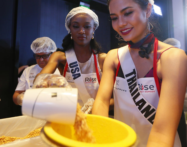 Miss Universe contestants Deshauna Barber of the United States and Chalita Suansane of Thailand help pack meals for distribution to the needy in suburban Pasay city southeast of Manila, Philippines Wednesday, January 18, 2017. (Photo by Bullit Marquez/AP Photo)