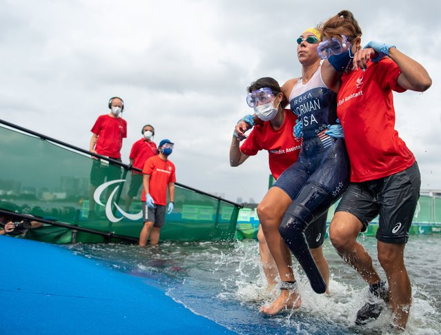 A handout photo made available by OIS/IOC shows Grace Norman of the USA being helped to exit the water in the Women's Triathlon PTS5 at Odaiba Marine Park during the Tokyo 2020 Paralympic Games in Tokyo, Japan, 29 August 2021. (Photo by Joel Marklund for OIS/EPA/EFE)