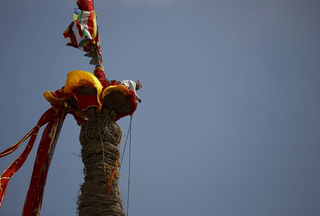 A devotee climbs on top of the chariot of Rato Machhindranath to fix ropes during the chariot festival at Bungamati in Lalitpur April 22, 2015. (Photo by Navesh Chitrakar/Reuters)