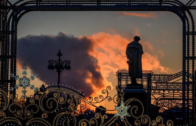 The sun lightens the clouds of steam from a local power plant behind a monument of Russian poet Alexander Pushkin in downtown Moscow on January 9, 2019. (Photo by Mladen Antonov/AFP Photo)