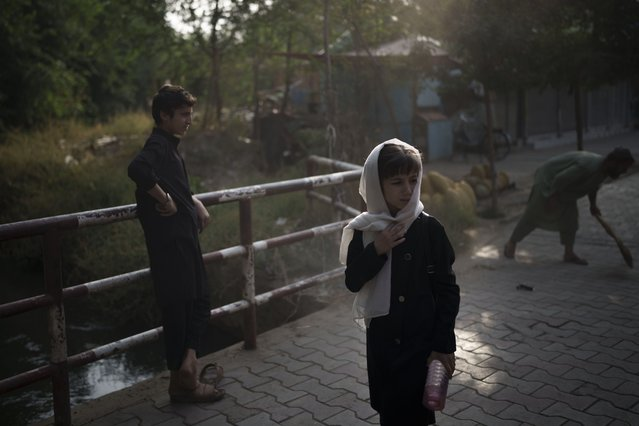 A girl waits for her friends as they walk to school in Kabul, Afghanistan, Sunday, September 12, 2021. (Photo by Felipe Dana/AP Photo)