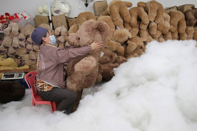 A worker stuffs a toy bear with cotton at a toy factory in Wuhan, on January 16, 2014. (Photo by Reuters/Stringer)