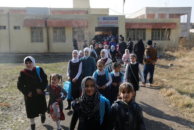 Schoolchildren leave after registering at a school and receiving their new school bags in Mosul, Iraq, January 23, 2017. (Photo by Muhammad Hamed/Reuters)