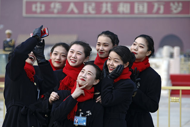 Hospitality staff take selfies on Tiananmen Square during the opening session of the Chinese People's Political Consultative Conference (CPPCC) held at the Great Hall of the People in Beijing, Sunday, March 3, 2019. (Photo by Andy Wong/AP Photo)
