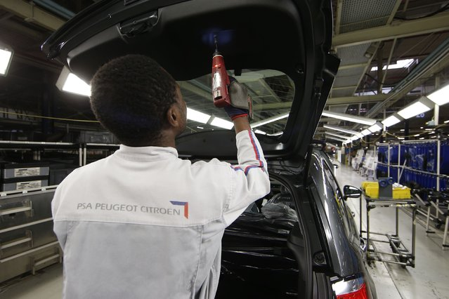 An employee works on the automobile assembly line of a Citroen C3 car at the PSA Peugeot Citroen plant in Poissy, near Paris, France, April 29, 2015. (Photo by Benoit Tessier/Reuters)