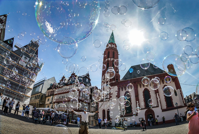 A street artist makes soap bubbles in front of the Alte Nikolaikirche church at the Roemerberg square in Frankfurt am Main, western Germany, on August 12, 2018. (Photo by Frank Rumpenhorst/DPA/AFP Photo)