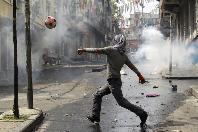 A protester plays with a ball during clashes with police in Okmeydani neighborhood in Istanbul, Turkey, May 1, 2015. (Photo by Huseyin Aldemir/Reuters)
