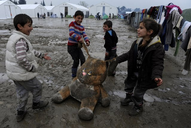 Refugee children play with a stuffed toy at a muddy makeshift camp at the Greek-Macedonian border, near the village of Idomeni, Greece March 15, 2016. (Photo by Alexandros Avramidis/Reuters)