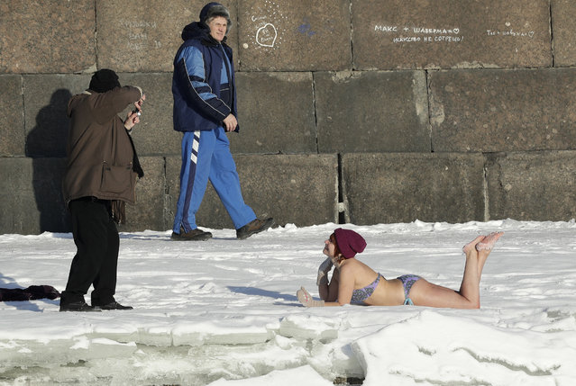 A man takes a photo of a woman sunbathes on snow near the wall of St.Peter and Paul Fortress in St.Petersburg, Russia, Tuesday, February 7, 2017. The temperature in St. Petersburg is minus 12 degrees Centigrade (10 degrees Fahrenheit). (Photo by Dmitri Lovetsky/AP Photo)