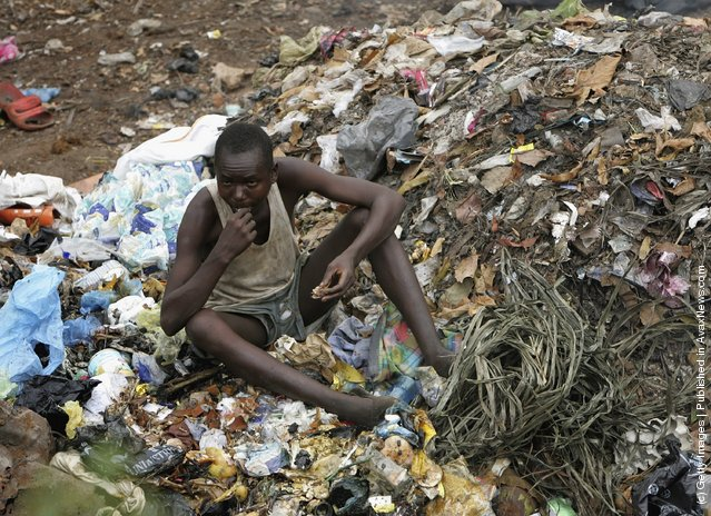 A Man eats garbage from a pile in Freetown, Sierra Leone