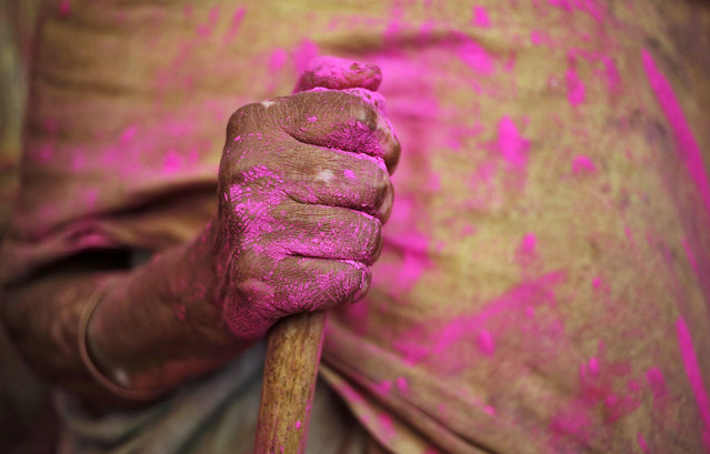 A widow daubed in colours holds a stick as she takes part in the Holi celebrations organised by non-governmental organisation Sulabh International at a temple at Vrindavan, in the northern state of Uttar Pradesh, India, March 21, 2016. (Photo by Anindito Mukherjee/Reuters)