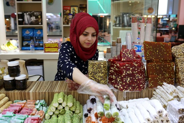 "In this Wednesday, April 30, 2015 photo, Rahaf Abdullah works at a sweets shop at a mall in Irbil, in Iraq's Kurdish region. Two years after fleeing from her home in Damascus, the 22-year-old is selling sweets to local women who largely refuse to take such jobs. ""The Kurdish girls are a bit conservative. No, a lot conservative"", she says. (Photo by Bram Janssen/AP Photo)"